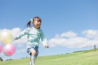 複数の風船を持って走っている日本人の女の子