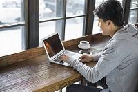 カフェでパソコンを操作する若者