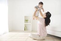 リビングで赤ちゃんを抱っこするお母さん