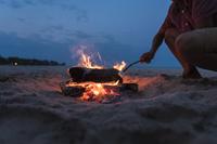 マシュマロを焚き火で炙る若者の男性