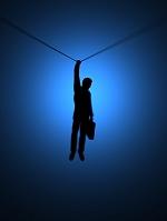 ロープにぶら下がるシルエットのビジネスマン