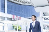 空港の前を歩くミドル世代の日本人ビジネスマン