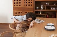 椅子につかまって屈みこむ腰痛の女性