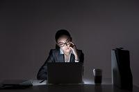 暗い部屋でラップトップを眺める女性