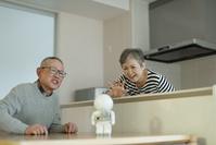 コミュニケーションロボットに話しかける老夫婦