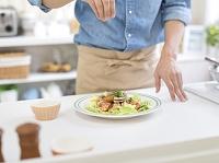 料理を盛り付ける日本人男性の手