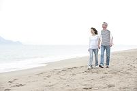 海辺で砂浜を歩く中年夫婦カップル