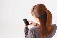 携帯を操作するビジネスウーマン