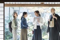 住職にお寺を案内される日本人女性