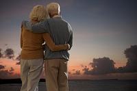 肩を組んで日没を見守る外国人のシニア夫婦