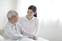 ベッドに座るシニアと日本人女性介護士