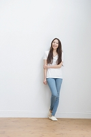 壁に寄り掛かる白いTシャツとデニムの若い日本人女性