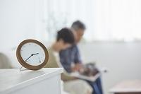 置き時計とリビングの日本人シニア夫婦