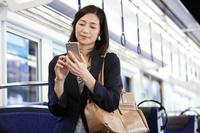 通勤電車でスマートフォンを操作するビジネスウーマン