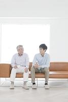 ソファに座っる笑顔の父親と息子