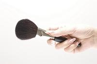 化粧ブラシを持つ女性の手