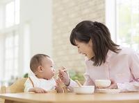 離乳食を息子に食べさせる母親