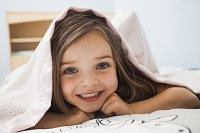 ブランケットを被った笑顔の少女