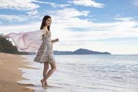 海辺で布をまとう若い女性