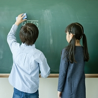 黒板で算数の問題を解く日本人の小学生の男の子と女の子