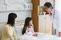 病室で医者の診察を受ける女の子