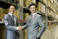 倉庫内で握手をするビジネスマンたち