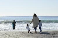 サーフィンをする父親と見守る家族