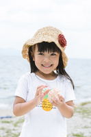 砂浜で貝殻を持った女の子