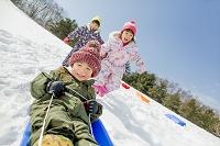 雪の公園でソリ遊びをする日本人の子供たち