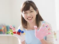 手袋シアターをはめて笑う保育士