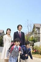 住宅街を歩く入学の日の家族