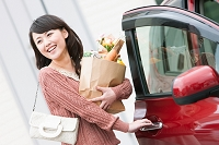 車のドアを開ける笑顔の日本人女性