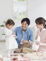 子供の着替えを手伝う夫婦