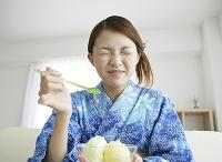かき氷を食べる浴衣を着た女性