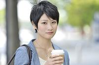 街中でコーヒーを持つ女性