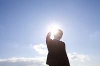 太陽に手をかざすビジネスマン