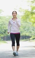 新緑の中でウォーキングをする日本人女性