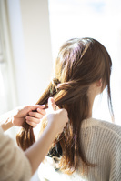 髪の毛を結ぶ女性の後ろ姿