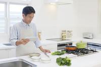 タブレットを見ながら朝食を作る中年男性