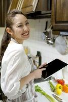 キッチンでタブレットを持つ20代日本人女性