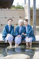 足湯する浴衣と羽織の母と娘と姑