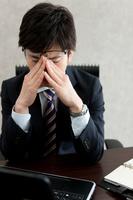 目元を押さえる日本人ビジネスマン