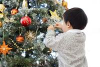 クリスマスツリーに飾り付けをする男の子