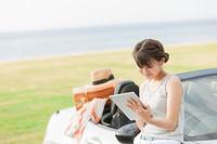 車の前でタブレットを操作する女性