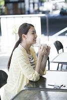 カフェテラスでくつろぐ20代日本人女性横顔