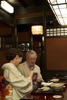 外国人に日本酒を注ぐ着物の女性