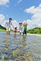夏の河原で水遊びの家族