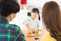 おやつを食べようとする女の子と両親