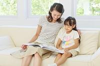 ソファーで本を読む母子