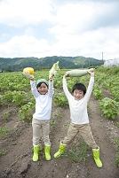 畑で収穫した野菜を持つ日本人の子供